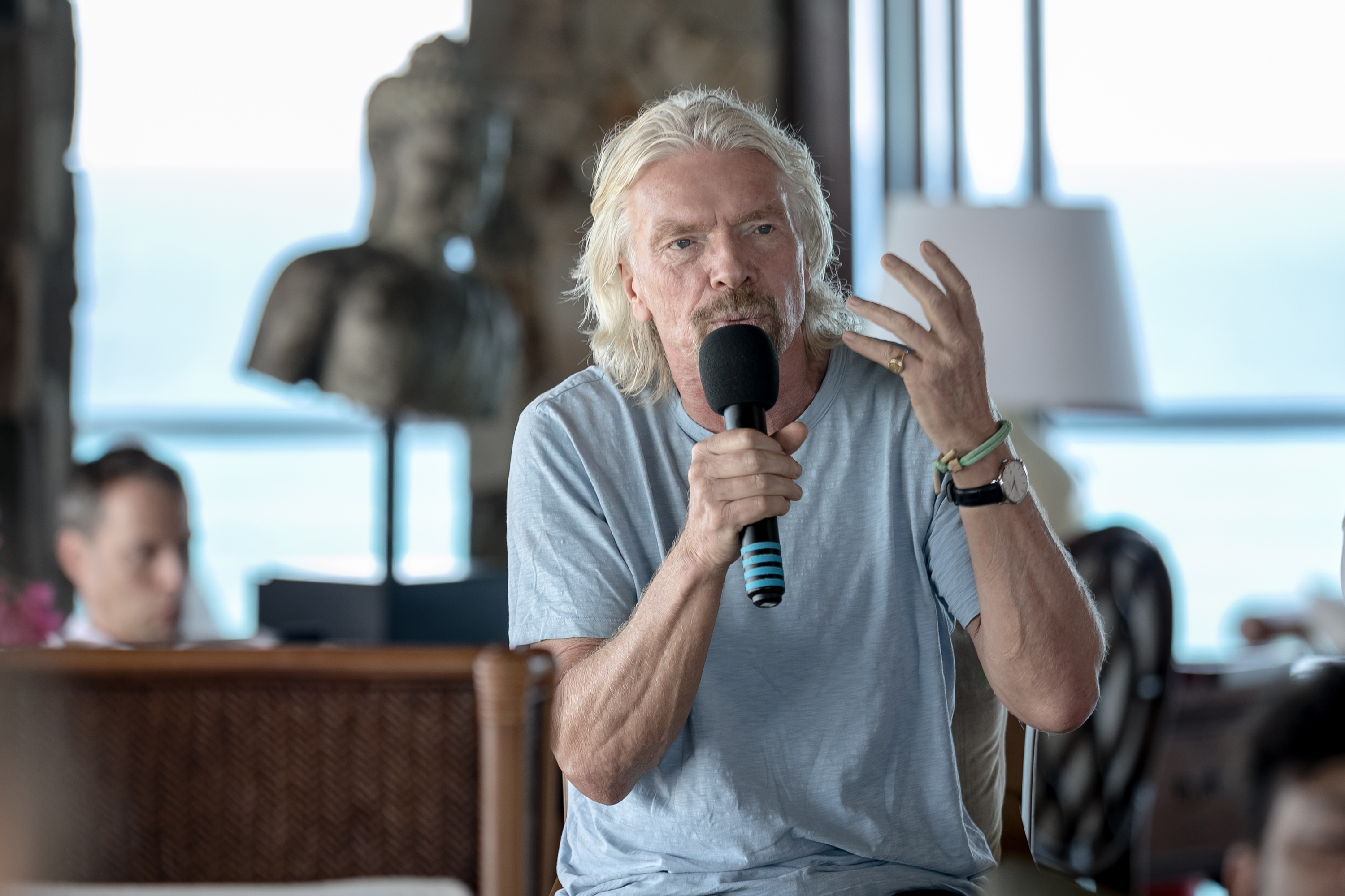 Sir Richard Branson wearing goggles riding a foilboard with a kite at sea