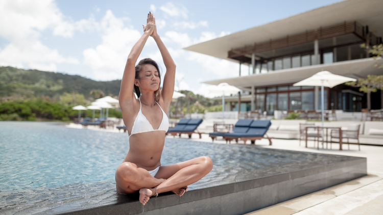 Paula Rosales doing yoga in a white bikini at the pool in front of the Aman hotel