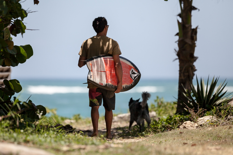 Brandon Sanford with a Volcom surfboard and a pet dog walking to the beach
