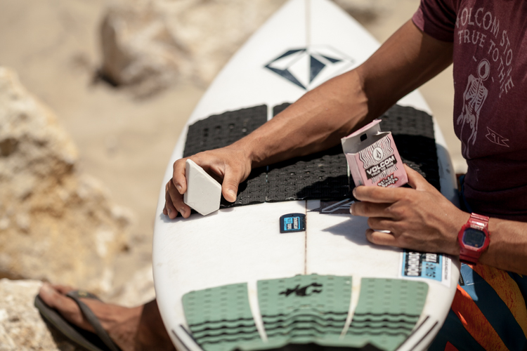 Close-up of Brandon Sanford waxing a surfboard with Volcom wax at the beach