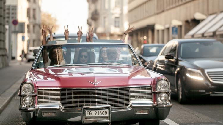 Sindia Rifi driving through Zurich in a pink Cadillac alongside models