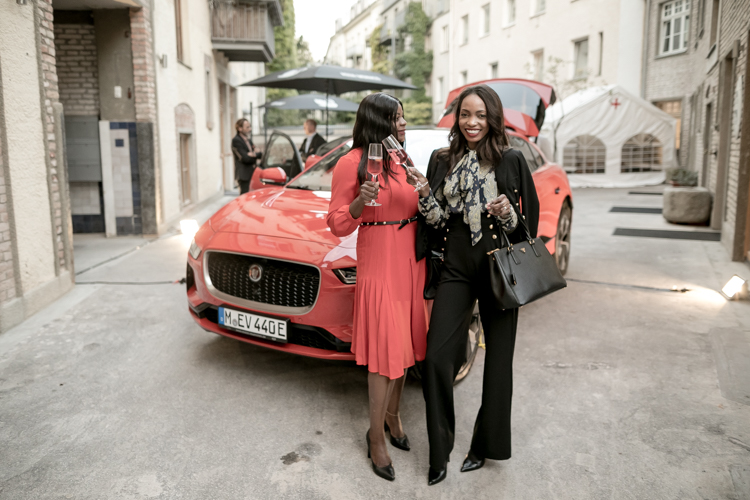 Two models toasting with rosé glasses in front of red Jaguar I-Pace sportscar