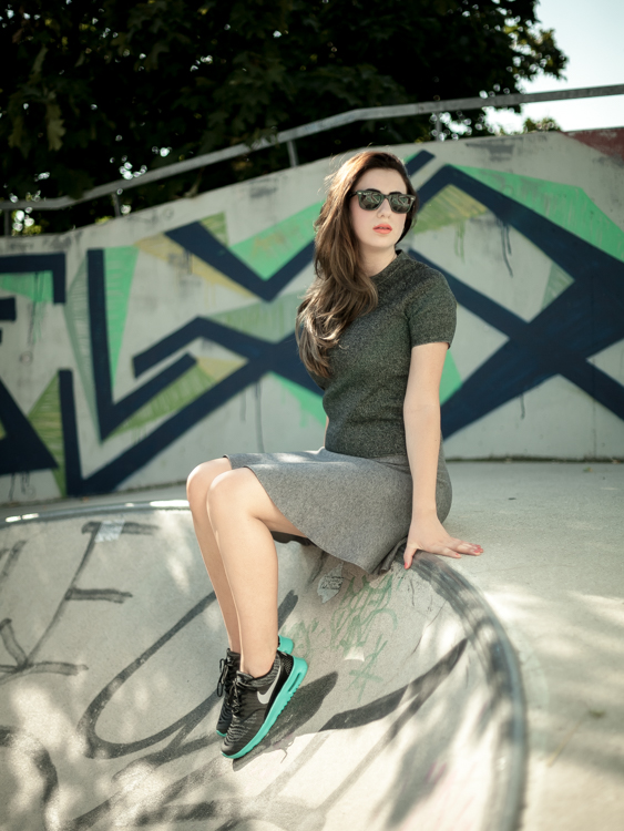 Sara in a green outfit and Nike sneakers sitting on the edge of a half pipe