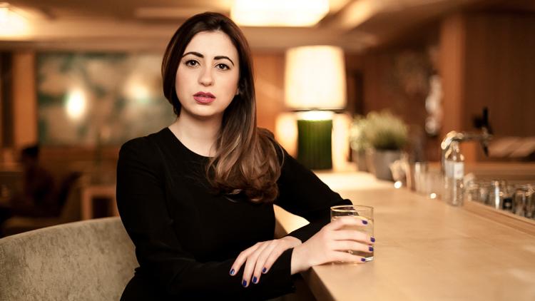 Portrait of Sara sitting at the hotel bar