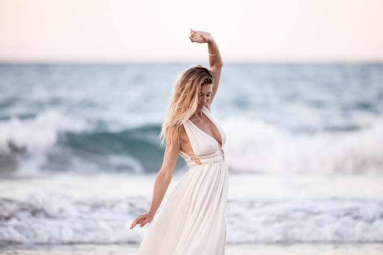 Model in a white dress posing in front of the caribbean ocean at sunset
