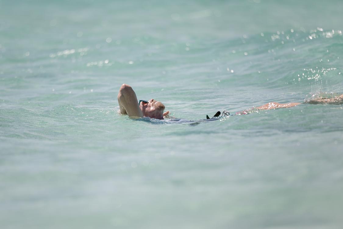 Sir Richard Branson bathing his head in ocean water