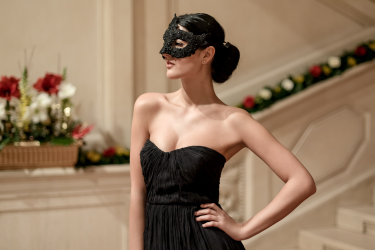 Portrait of a model in a black evening dress and a classical mask at the Hofburg in Vienna.
