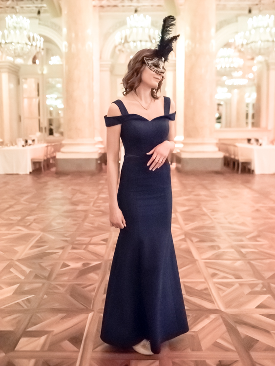 Portrait of a tall model in a blue evening dress and a classical mask in a lit hall of the Hofburg in Vienna.