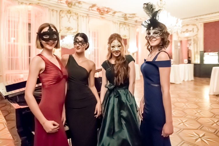 Models in evening dresses and classical masks in front of a piano in a lit hall of the Hofburg in Vienna.