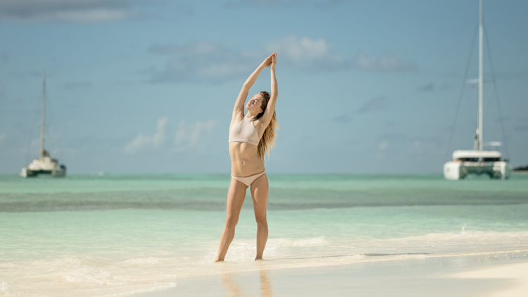 Sierra Quitiquit in a bikini doing yoga at a caribbean beach with sailboats in the background