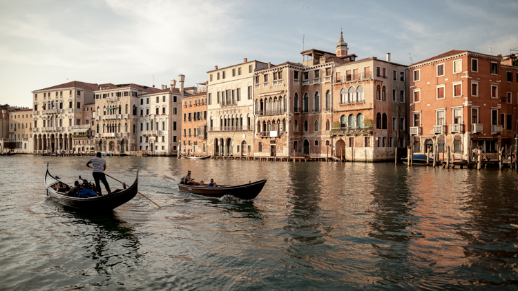 Houses in Venice reflecting in the channel with gondolas passing in the foreground.